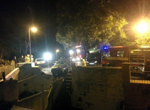 Car crashes through stone wall