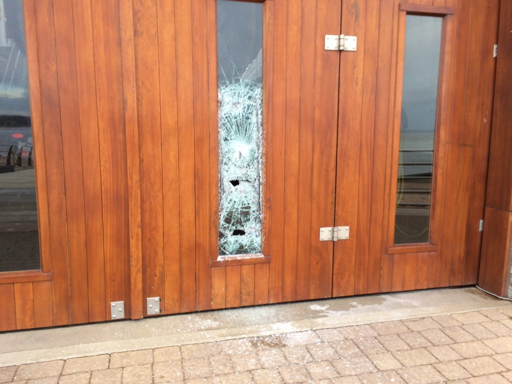 Photo Credit: Exmouth RNLI.  Smashed window on the all-weather lifeboat hall door.