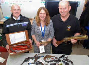 Chief Inspector Daniel Evans with antique duelling pistols, Firearms and Explosives Licensing Manager Michelle Mounsey with WW1 flare pistol, Armourer Mike Barker with replica blunderbuss.