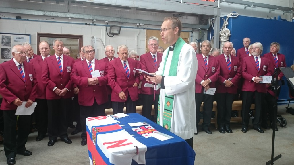 Station Chaplain, Rev. James Hutchings addresses the congregation with the Budleigh Salterton Male Voice Choir in the background.