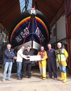 Casualties hand over a cheque to station volunteers who played a part in their rescue. L to R: Deputy Launching Authority, Neil Matson; Casualties, Richard Smith and Jared Colclough; Coxswain, Steve Hockings-Thompson; Mechanic, Mark Sansom and Tractor Driver, Neil Cannon. (credit: Exmouth RNLI)