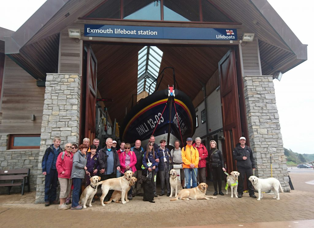 Derek and Neil with their visually impaired visitors, helpers and dogs in front of Exmouth lifeboat station. Photo: Exmouth RNLI