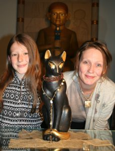 Artists Sophie Bryett-Smith (aged 8, of Preston Primary School) & Amie Schofield (of Torquay Museum) with Cleo the Egyptian Cat