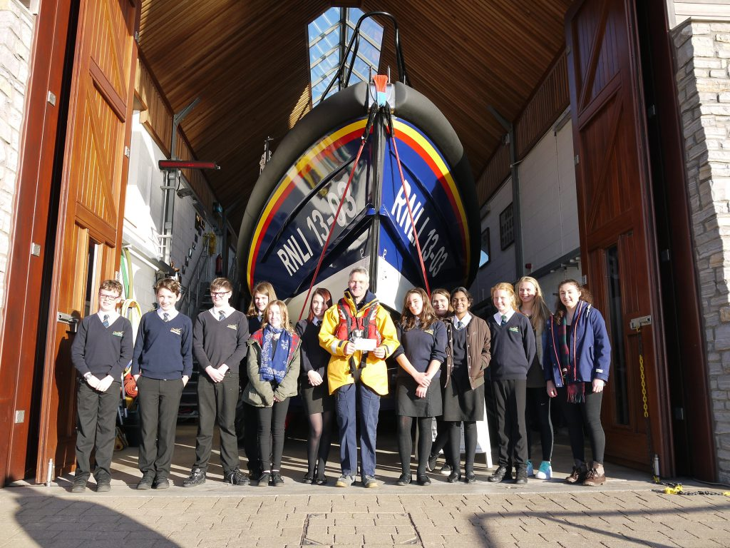 Clyst Vale students handing over the cheque to Coxswain, Steve Hockings-Thompson in front of Shannon class lifeboat R and J Welburn