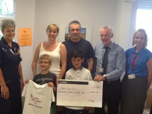 Jake and Finn hand over the cheque to staff at the BCU