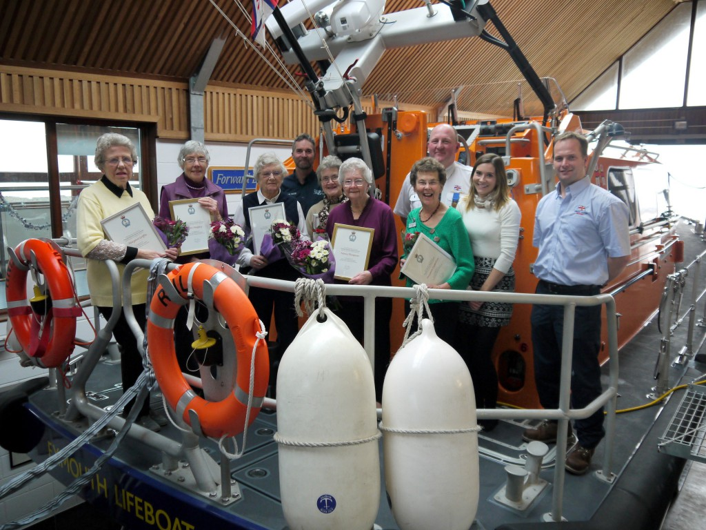 L to R: Margaret Griffin, Anne Midgley, Jill Carter, Coxswain Steve Hockings-Thompson, Barbara Davies, Nancy Thompson, Margaret Eaglesham, Deputy Coxswain Roger Jackson, Visitor Experience Manager Amanda Woods and Mechanic Andy Williams. [Photo Credit: Exmouth RNLI]