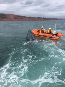 Inshore lifeboat, George Bearman crew volunteers stay on scene to watch over the sinking motorboat. Photo Credit: Exmouth RNLI
