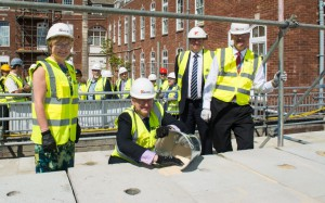 (front from left to right) Mairead McAlinden, CEO South Devon Healthcare NHS Foundation Trust; Sir Richard Ibbotson, Chairman South Devon Healthcare NHS Foundation Trust, fixing the last block in place; Simon Parsons, Kier and Dr David Sinclair, Deputy Medical Director South Devon Healthcare NHS Foundation Trust. (Back) Patients, community partners, and past and present hospital staff.