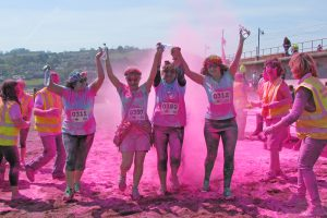 Participants get blasted with powder paint at the pink paint station on Teignmouth Beach